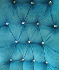 pikowane ozdobnymi guzikami oparcie fotela pluszowego